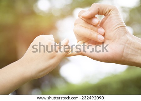 A mother and her child hooking their fingers to make a promise - stock photo