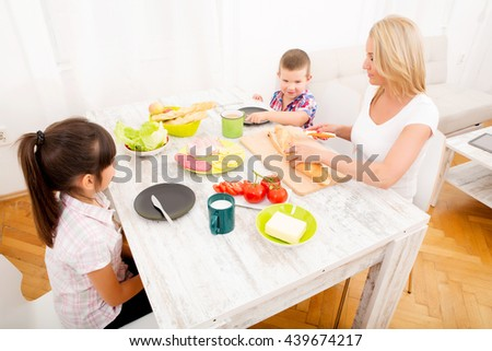A mother and her children having breakfast at home.