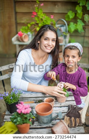 A mother and her daughter are repotting plants at the garden table - stock photo