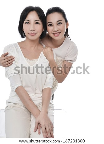 A mother and her daughter hugging. Posing on white background - stock photo
