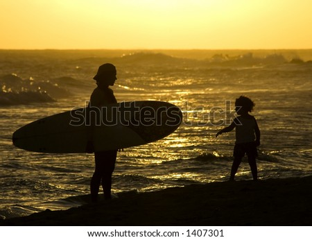 A mother and her daughter on the beach after Mom has spent the afternoon surfing in the Barbados waves. - stock photo