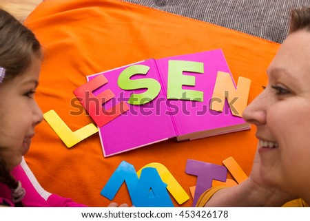 """A mother and her daughter while learning together """"lesen"""" (reading in german)   - stock photo"""