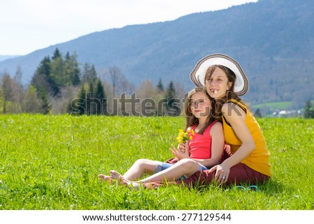 a mother and her daughter with a flower in his mouth in meadow