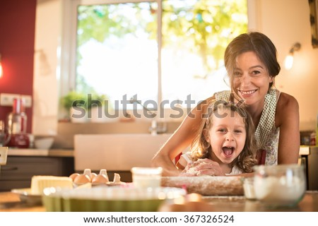 A mother and her four years old blonde daughter are cooking in a luminous kitchen. They are having fun, working on a pastry with a rolling pin on a wooden table full of ingredients and a baking pan. - stock photo