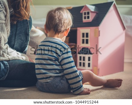 A mother and her son are playing with a doll house