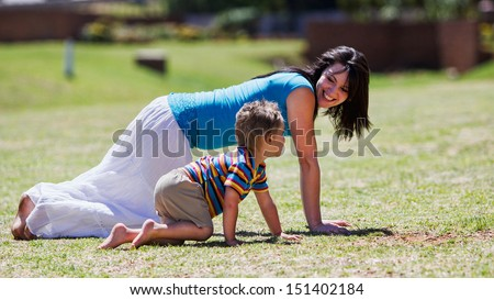 A mother and her son crawling and playing on the grass in summer. - stock photo