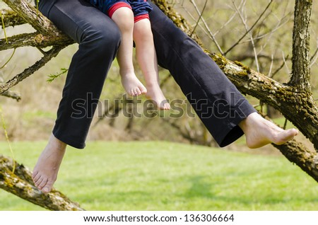 A mother and his little son relaxing in a tree - stock photo