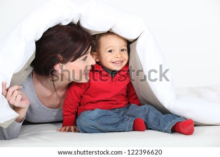 A mother and his son under a blanket. - stock photo