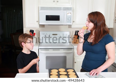 a mother and son enjoy fresh baked peanut butter cookies after school in the kitchen - stock photo