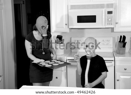 a mother and son enjoy hot fresh baked cookies in their kitchen while wearing gas masks in a post nuclear future in black and white for a edgy futuristic image - stock photo