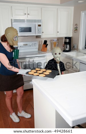 a mother and son enjoy peanut butter cookies in their kitchen while wearing gas masks in a post nuclear winter future - stock photo