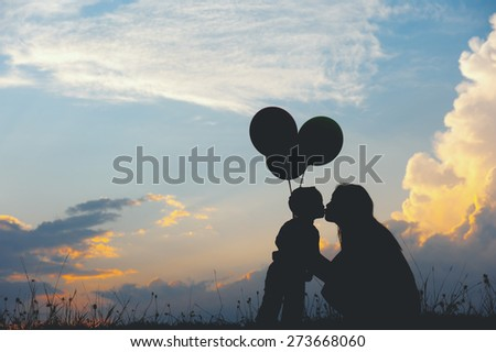 A mother and son kissing outdoors at sunset silhouette - stock photo