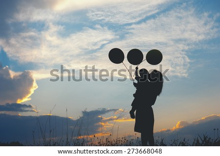 A mother and son playing outdoors at sunset silhouette - stock photo