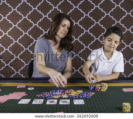 A mother and son sitting at a poker table learning how to play cards - stock photo