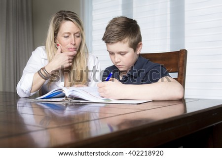 A mother at a table at home helping her small son with his homework from school