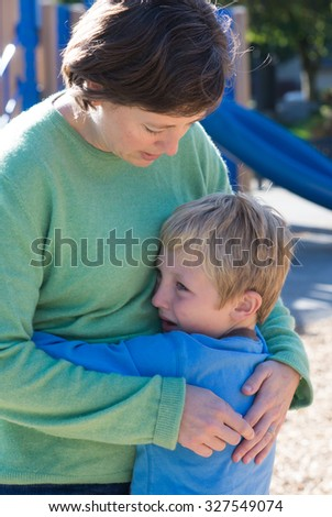 A mother consoles her son, perhaps over a playground altercation. - stock photo