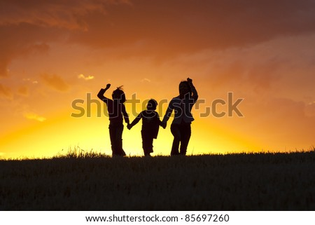 A mother, daughter, and son skip along at sunset.