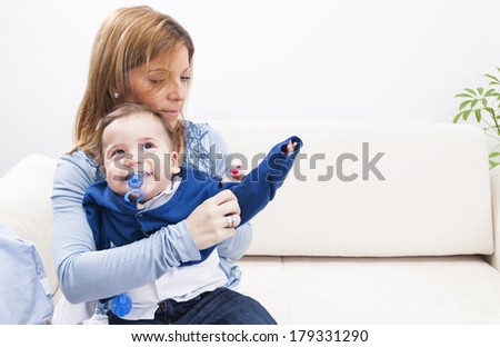 A mother dressing her serious boy at home - stock photo