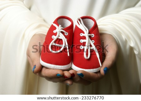A mother embraces her childs shoes to welcome a new beginning. - stock photo