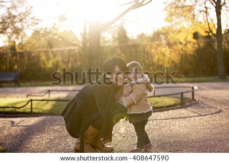 A mother embracing her baby girl in the park - stock photo
