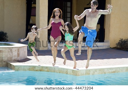 A mother, father and two children family having fun jumping into a swimming pool - stock photo