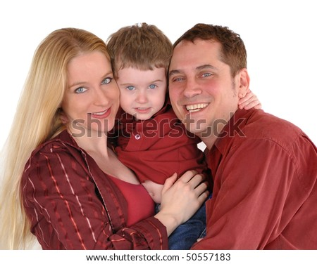 A mother, father and young son are standing together and hugging on a white background. and look very happy and smiling into the camera. They are wearing casual clothes. - stock photo