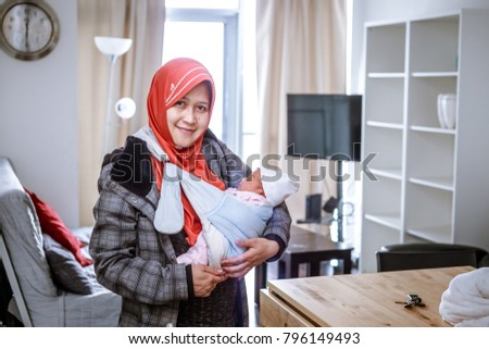 A mother from Indonesia with her newborn baby pose in and around their apartment in Toronto