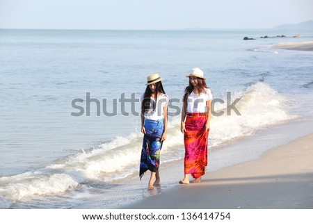 A mother having fun with her daughter on the beach - stock photo