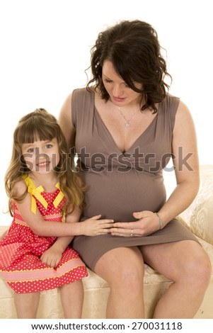 A mother helping her little girl feel the baby in her belly. - stock photo