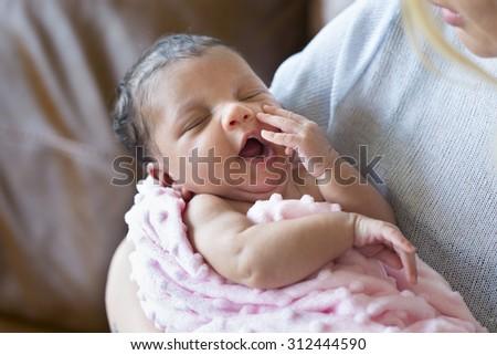 A mother holding her sleepy newborn baby girl.  - stock photo