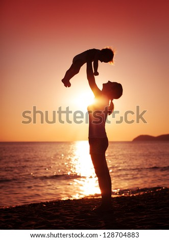A mother holding her young child up high.
