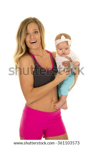 a mother holding on to her baby while she is working out.