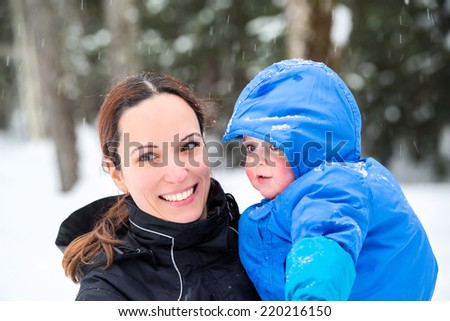 A mother holds her happy baby son outside while its snowing during the winter season.  - stock photo