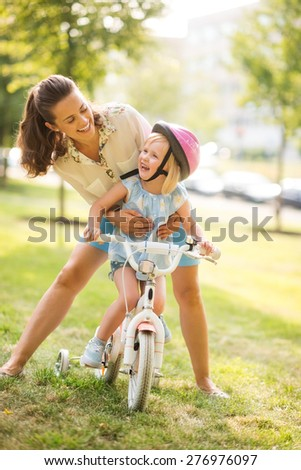 A mother hugs her daughter from behind, as daughter wearing a pink helmet looks up towards her mother, laughing and proud. She has just learned to ride her bike by herself, and is proud of herself.