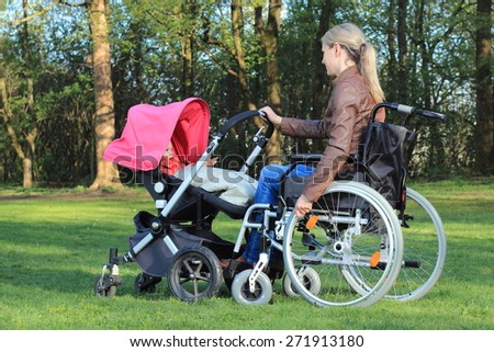 A Mother in wheelchair pushing a pram with baby - stock photo