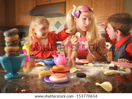 A mother is acting like a child and eating lots of junk food while her children are upset with her. There is a mess of chips, donuts and cookies. - stock photo