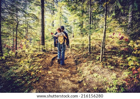 A mother is hiking on a trail in a forest with her baby in a back carrier during the autumn season.  Filtered to give retro, faded look.  - stock photo