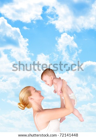 A mother is holding up her baby against a bright blue sky of clouds. Add your text to the empty copyspace. - stock photo