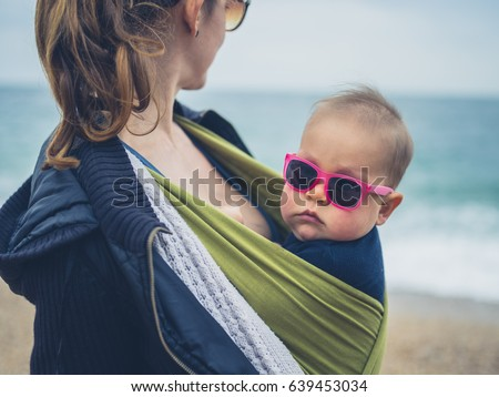 A mother is on the beach with her baby wearing sunglasses in a sling