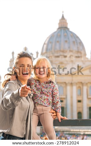 A mother is pointing at the camera, laughing and holding on her daughter who is sitting on a balustrade. The child has her arm around her mother's neck. In the background is St. Peter's Basilica. - stock photo