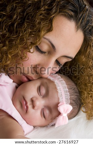 A mother kissing her daughter tenderly.