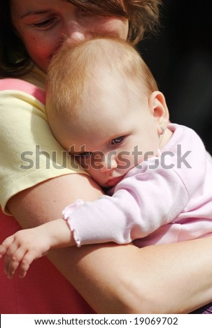 A mother kissing her tired cute baby daughter - stock photo