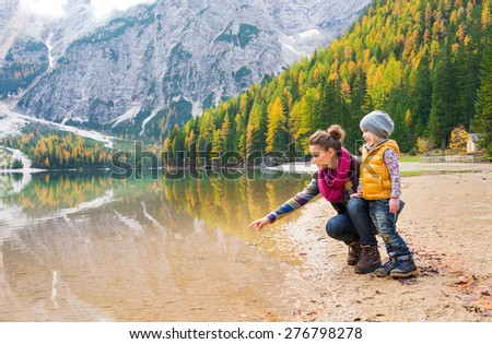 A mother, kneeling next to her daughter on the shores of Lake Bries, is pointing into the water. The colours of their hiking gear reflect the autumn foliage. - stock photo
