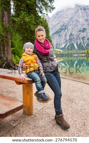 A mother leans on the wooden picnic table her daughter is sitting on. They are resting. Dressed in outdoor gear and hiking boots, they are smiling.