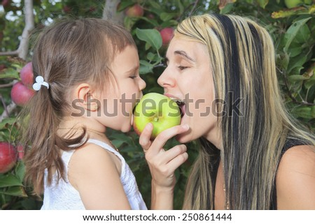 A mother playing with her daughter on apple tree - stock photo