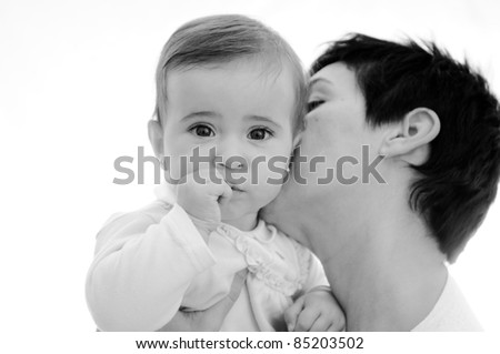 A mother playing with her little baby on white background in black and white