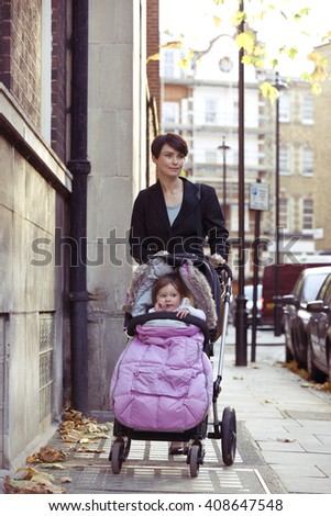 A mother pushing a stroller in the street - stock photo
