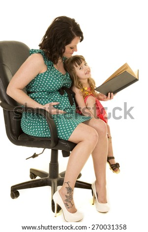 a mother reading a book to her little girl, with her hand on her pregnant belly. - stock photo