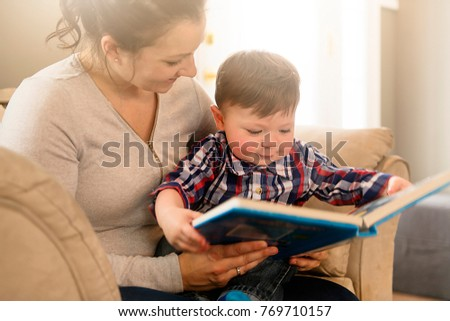 A Mother reading book with her child on sofa