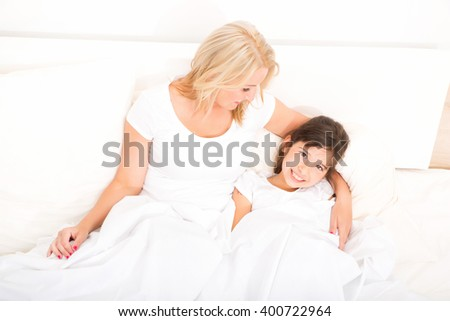 A mother relaxing in bed with her daughter.